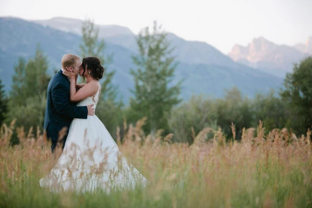 A bride and groom kissing in an open field with mountains in the background.