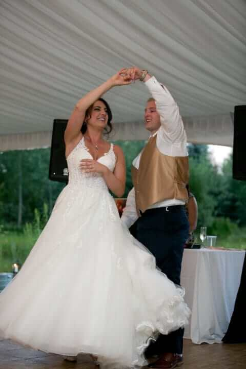 A groom twirling his bride during a dance at their reception.