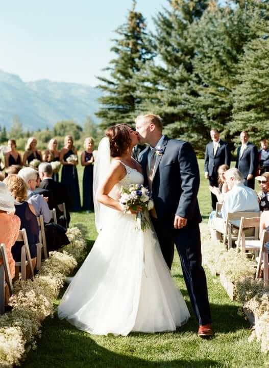 Bride and groom kissing in the aisle of their outdoor wedding ceremony.