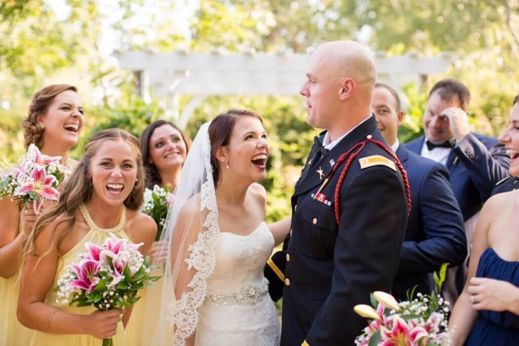 A bride and her groom looking excited while surrounded by a joyous bridal party.