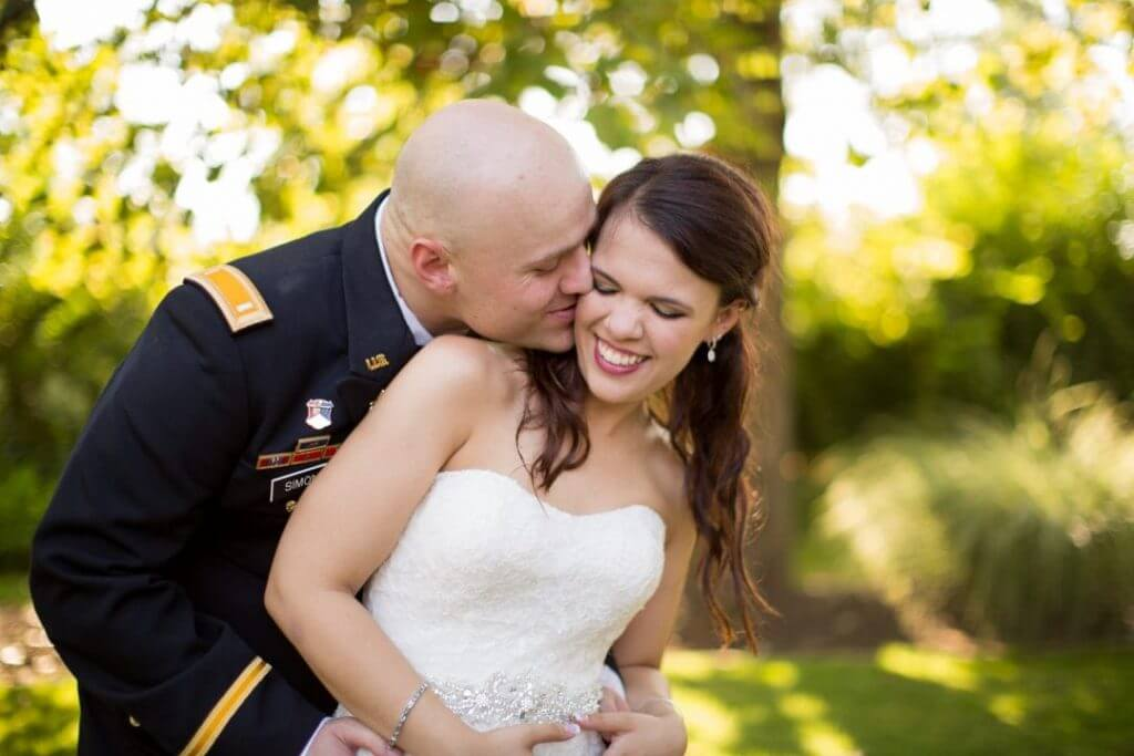 A groom embracing his bride from behind and kissing her on the cheek.