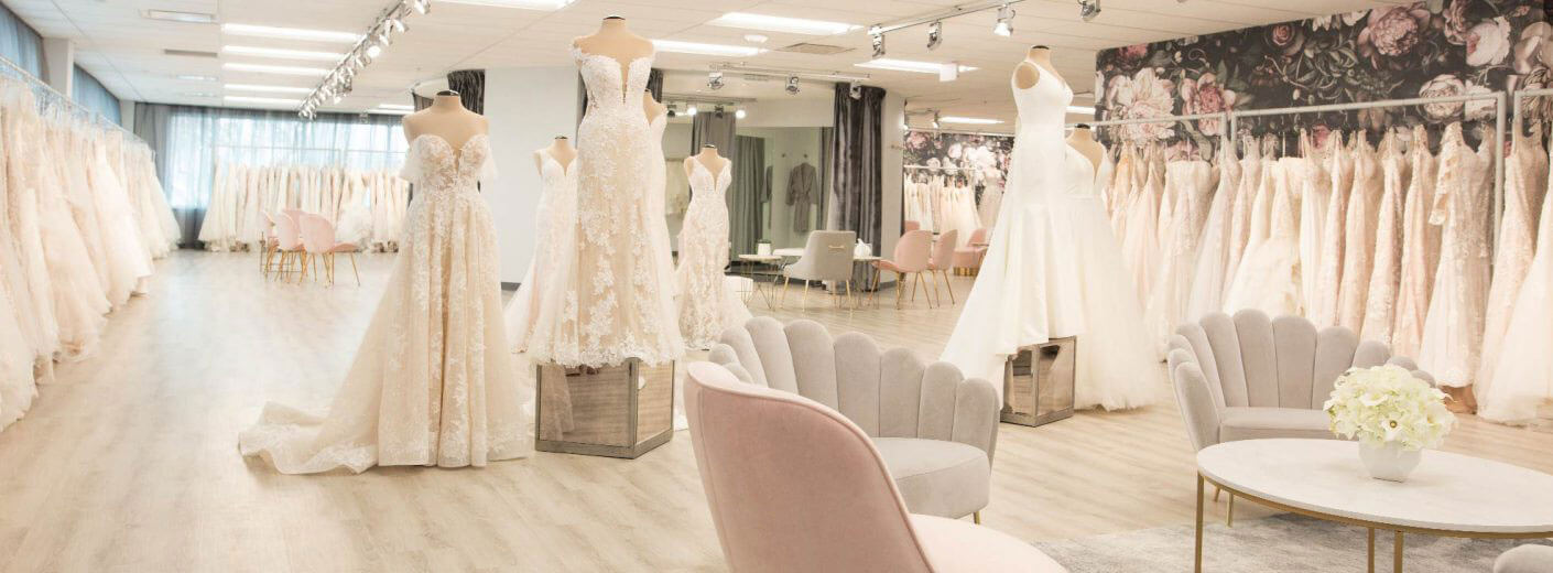 Interior photo of Belle Vogue Bridal, displaying the seating area, racks of wedding dresses, and mannequins wearing wedding dresses available to try on and purchase.