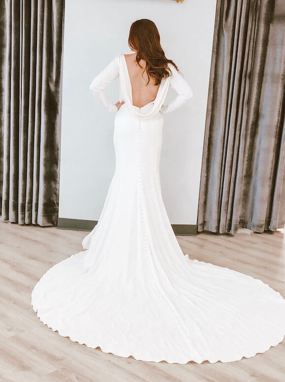 The back of a woman standing in a bridal boutique wearing a sleek long sleeved wedding dress by Martina Liana, style 791.
