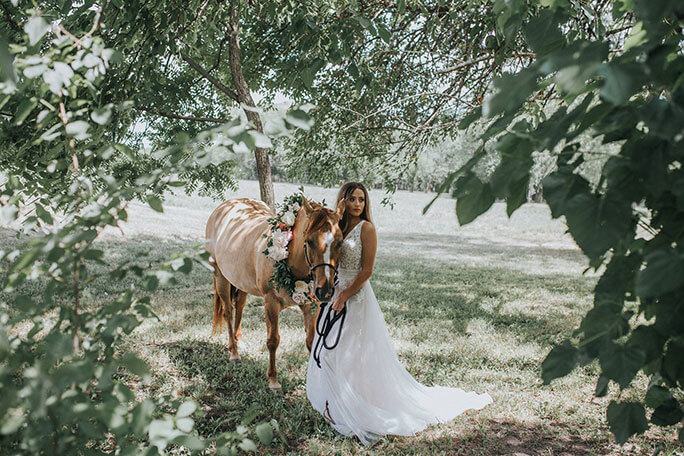 A bride in a boho wedding dress leading a horse through a wooded area.