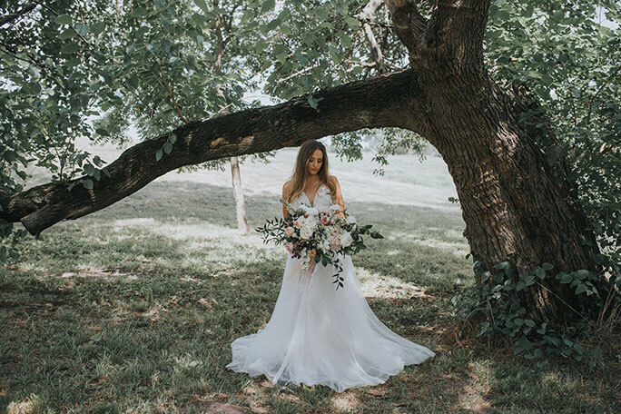 Bride wearing a boho wedding dress holding a large bouquet under a tree.