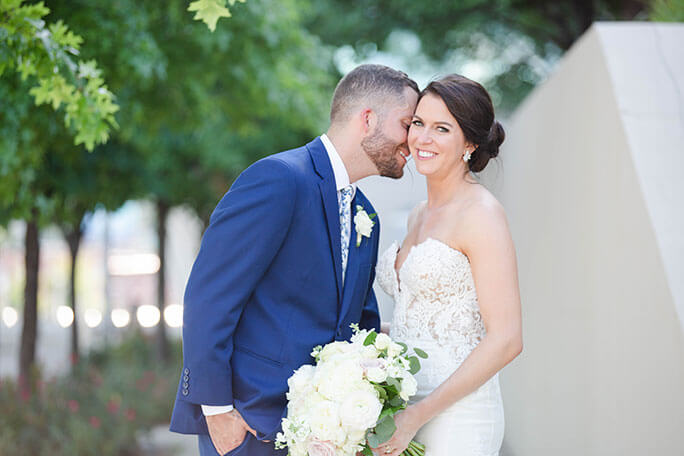 Real Bride Bonnie, standing outside with her husband, wearing a Martina Liana wedding dress, style 906.