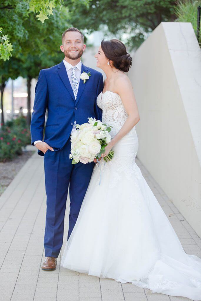Real Belle Vogue Bride Bonnie, standing on a sidewalk with her husband, wearing her Martina Liana wedding dress, style 906.