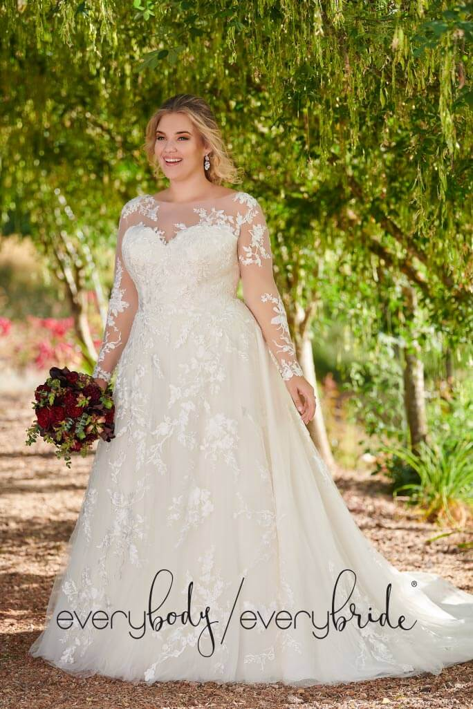 Plus size Bride standing outside wearning her long sleeved, lace, wedding dress from Essense of Australia, styleD2690+