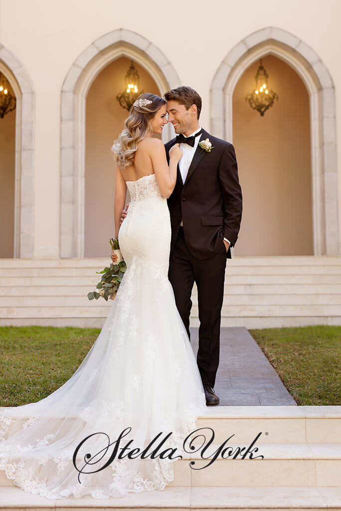 Bride standing on stairs with her groom, wearing a Stella York wedding dress, style 6867