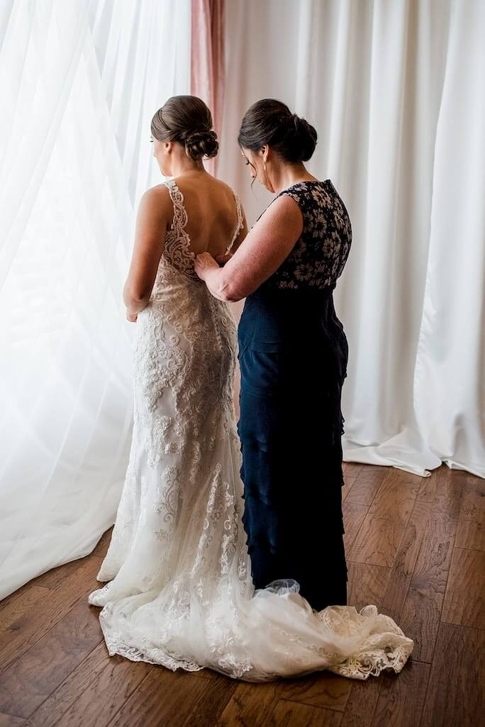 Real Bride Stephanie's Mother zipping her into her Essense of Australia wedding dress, style D2452.