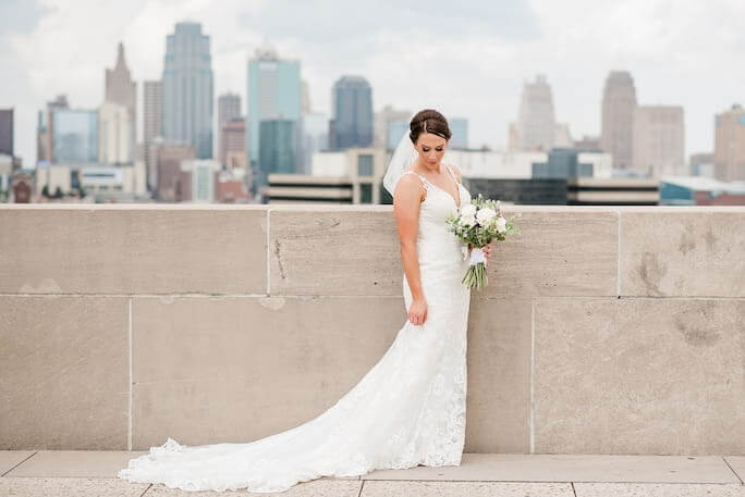 Real Bride Stephanie wearing her wedding dress from designer Essense of Australia, style D2452, standing on a rooftop with the Kansas City skyline in the background.