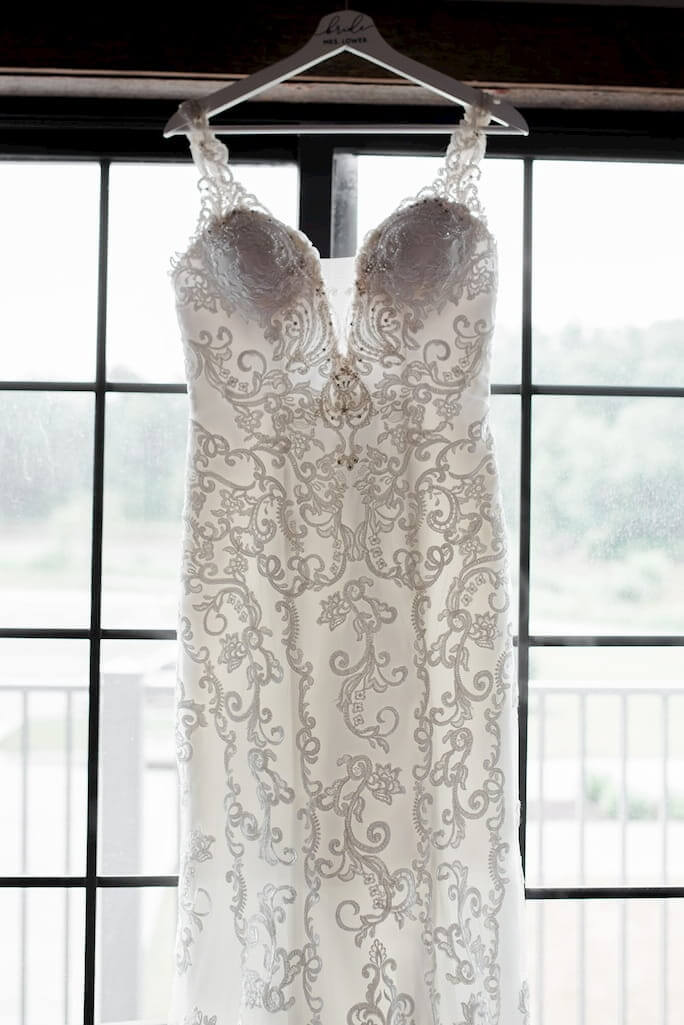 Real Bride Stephanie's Essense of Australia Wedding Dress, style D2452, hanging on a hanger in front of a window.