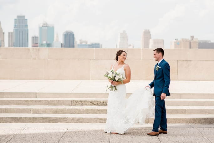 Real Bride Stephanie, with her husband Kory, posing with the Kansas City skyline behind them.
