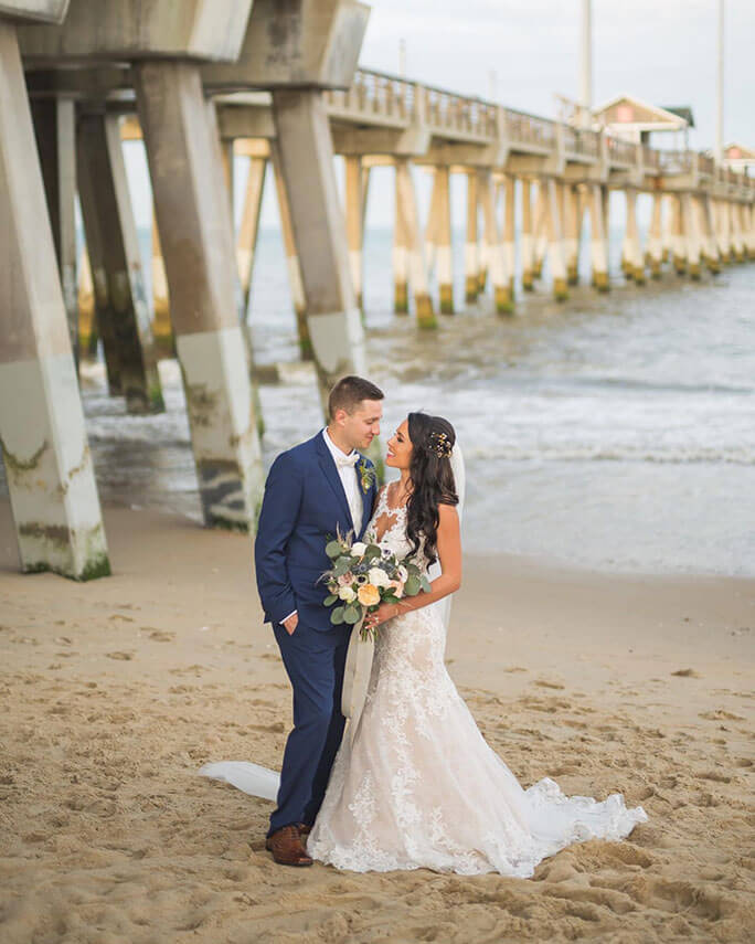 Bride Caroline posing on a beach wearing her Essense of Australia wedding dress, style D2548