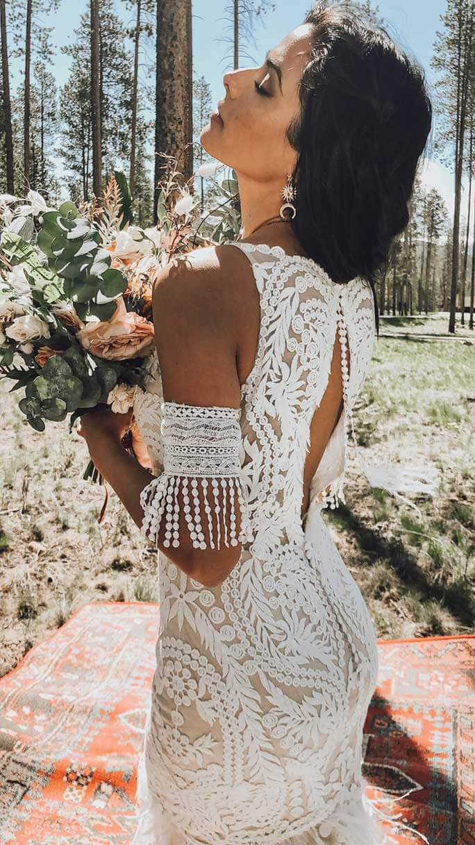 Boho bride outdoors wearing her Rowen wedding dress from All Who Wander.