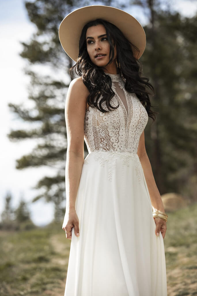 Bride pairing a wide-brimmed hat with her June wedding gown from the All Who Wander wedding gown collection