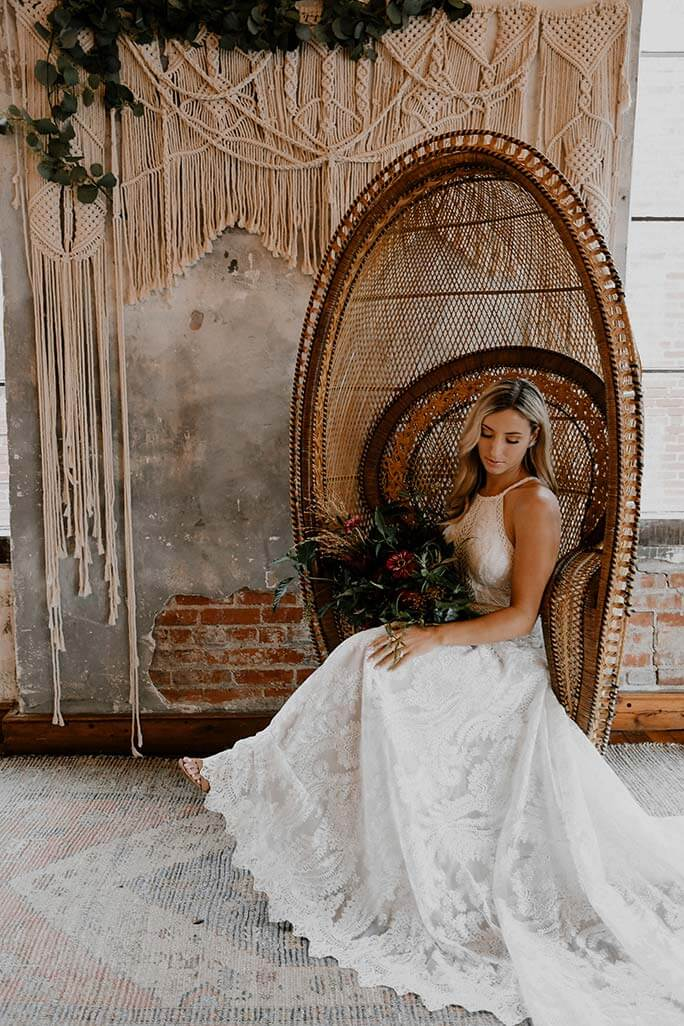 Boho bride sitting in her rattan chair, wearing the India wedding dress from the All Who Wander wedding gown collection