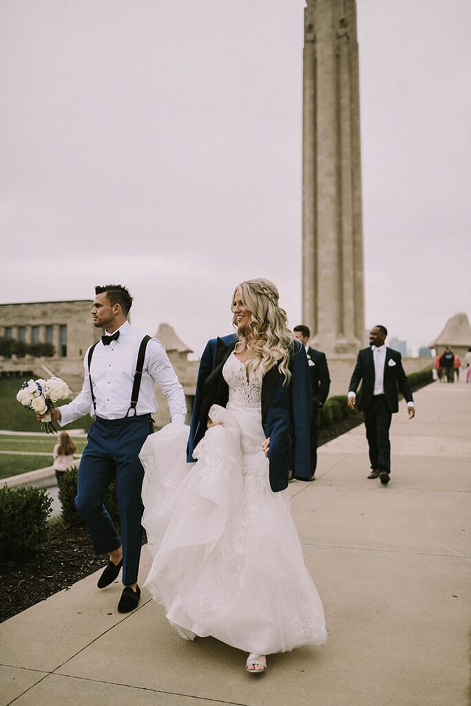 Real Belle Vogue Bride Brittany, wearing a Martina Liana wedding dress, walking down a side walk with the Liberty Memorial in the background.