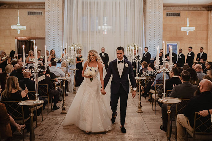 real Belle Vogue Bride Brittany walking down the aisle with her husband, wearing her Martina Liana wedding dress, style 906.