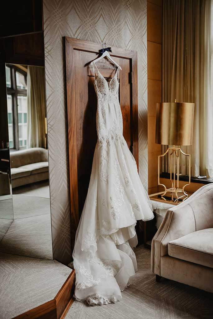 Real Belle Vogue Bride Brittany's wedding dress from Martina Liana, style 906, hanging on a door for display.