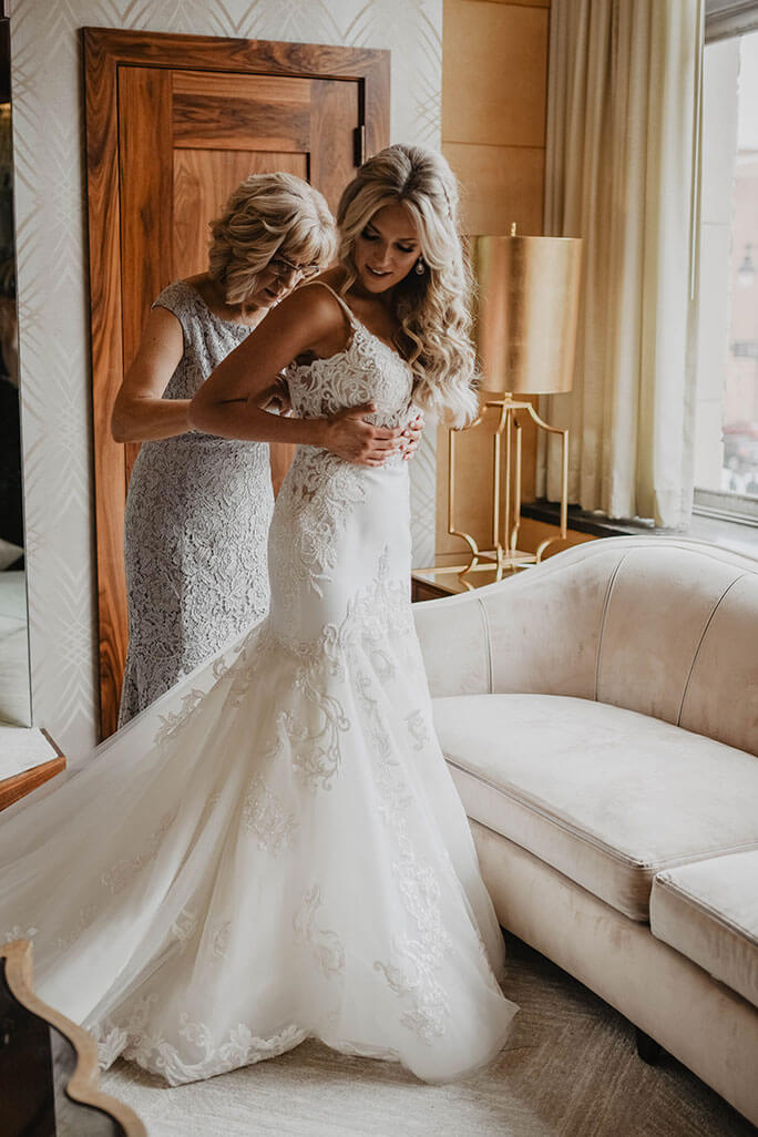Real Belle Vogue Bride Brittany's mom helping her tie the back of her Martina Liana, style 906 wedding dress.
