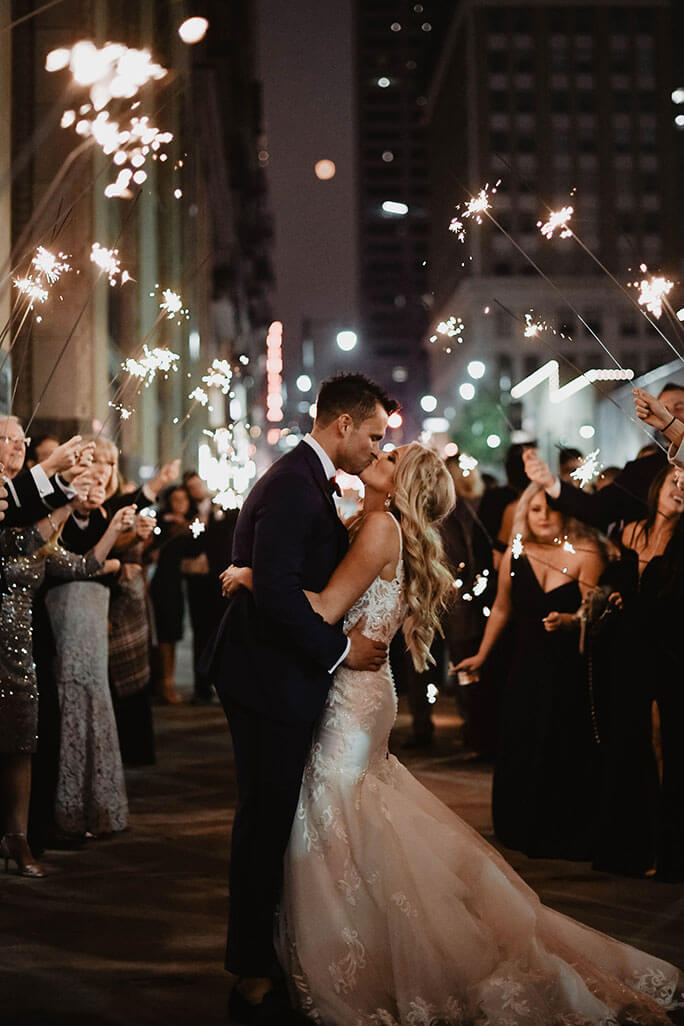 True Bride Brittany kissing her husband outside under sparklers. She is wearing a wedding dress by designer Martina Liana, style 906.