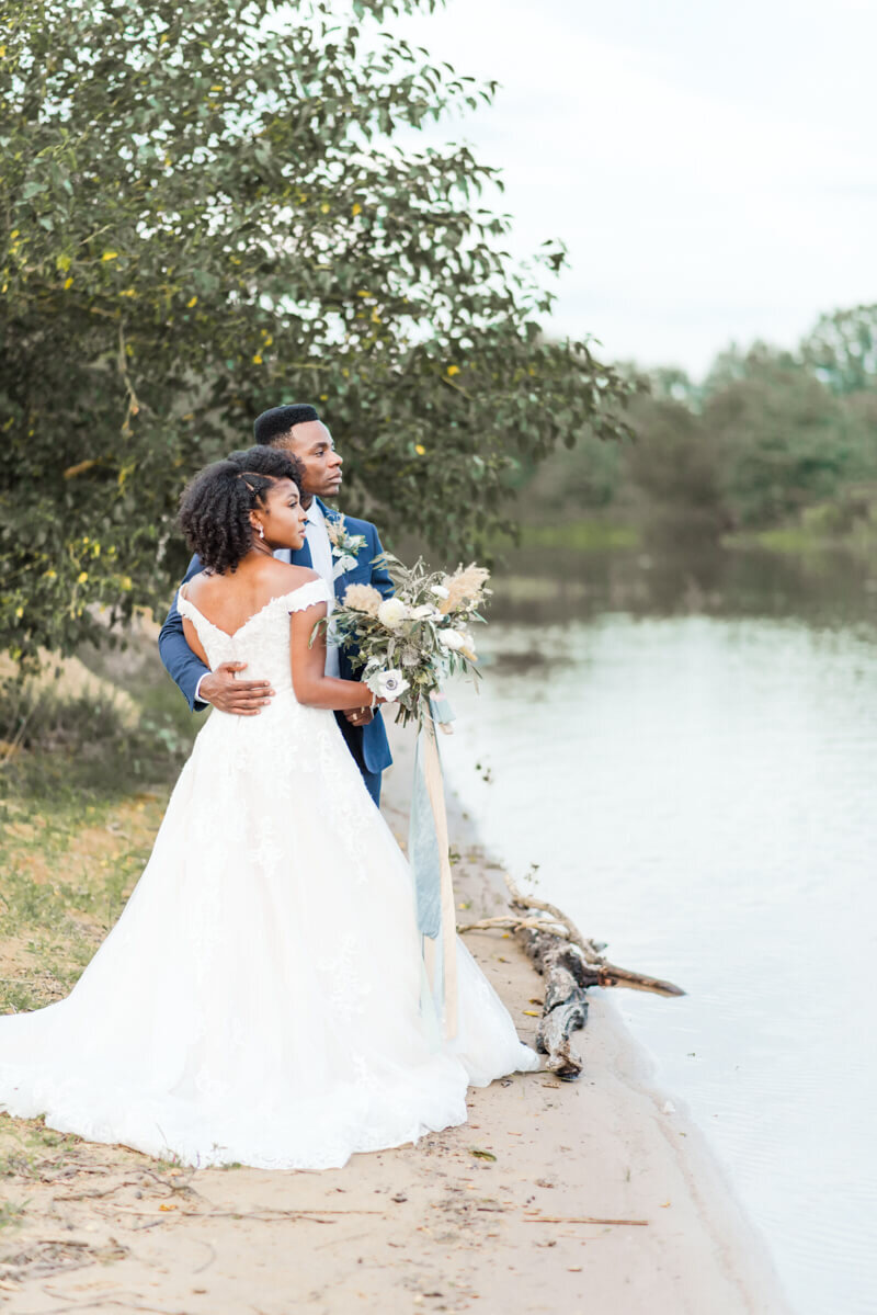 Trendy bride styled photo featuring groom and bride wearing essense of australia dress in style Style D2815 staring at the river