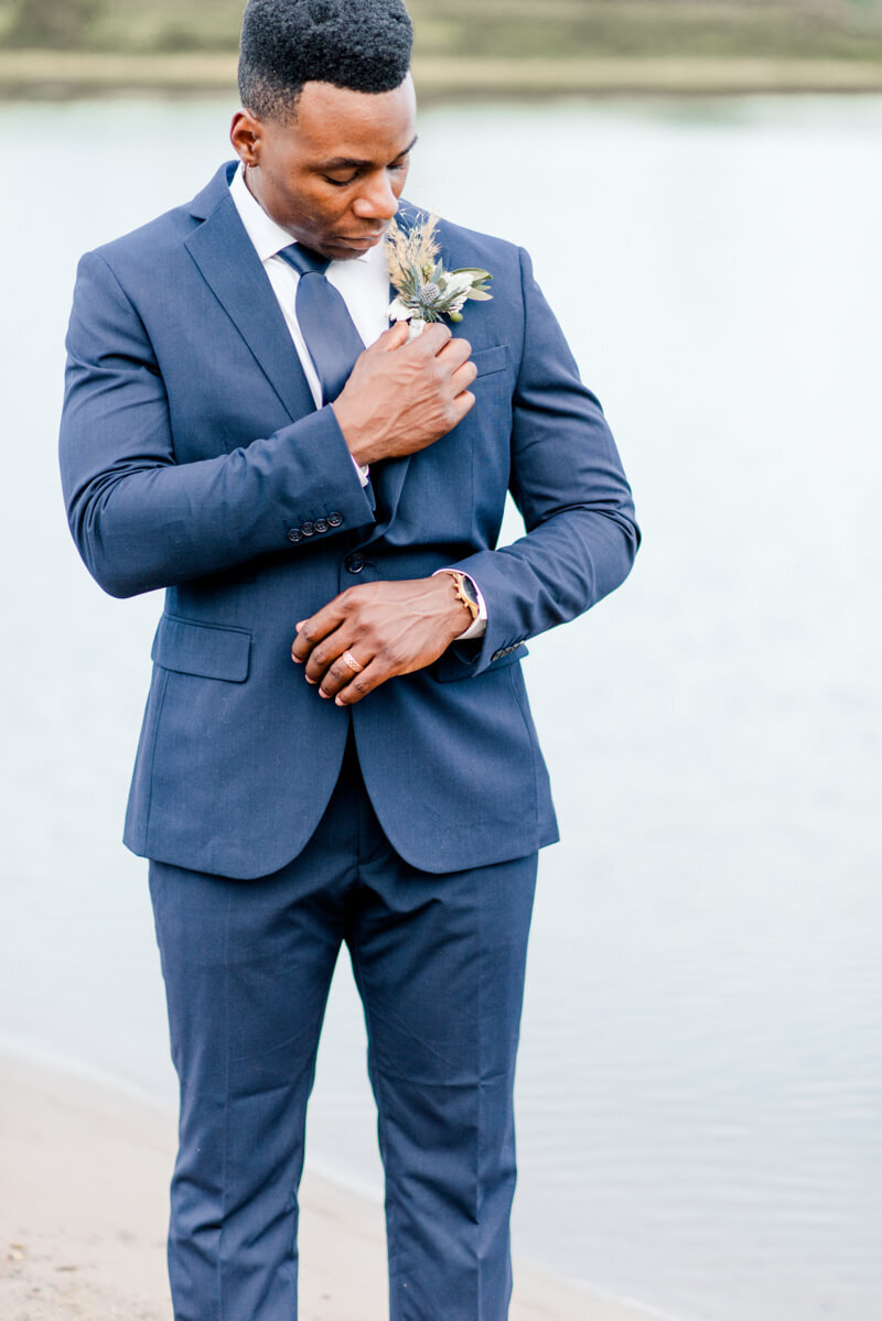 Trendy bride styled photo featuring groom fixing his suit