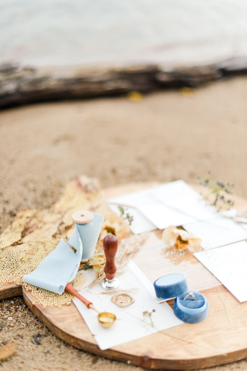 Trendy bride styled photo of wedding invitations with ocean background