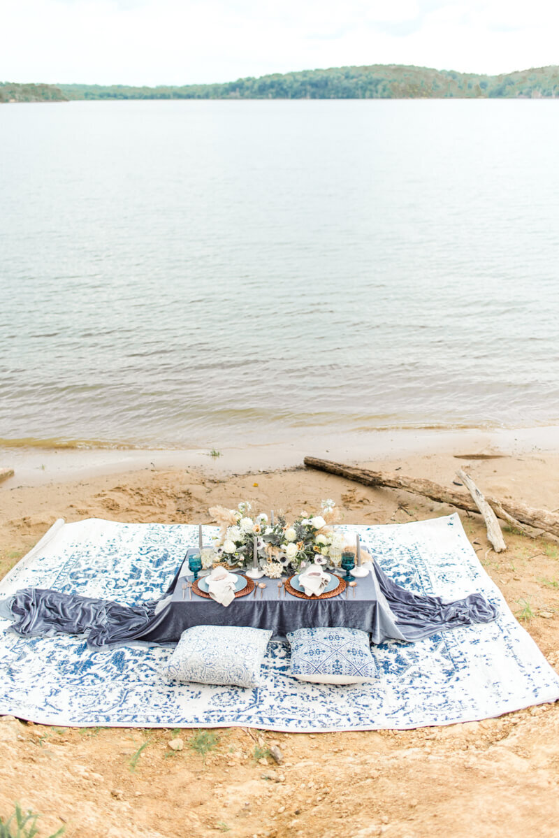 Trendy bride styled photo of table with wedding desserts and ocean background