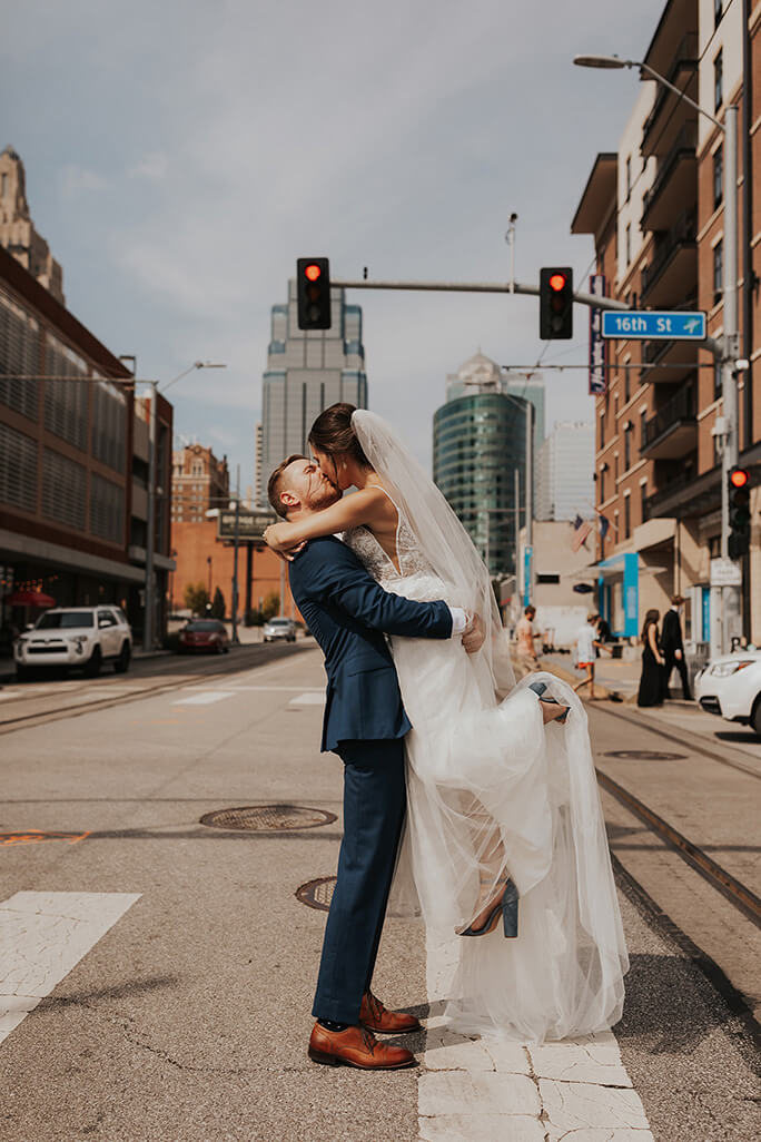 bride and groom sharing a kiss in the city - style D2840 by all who wander