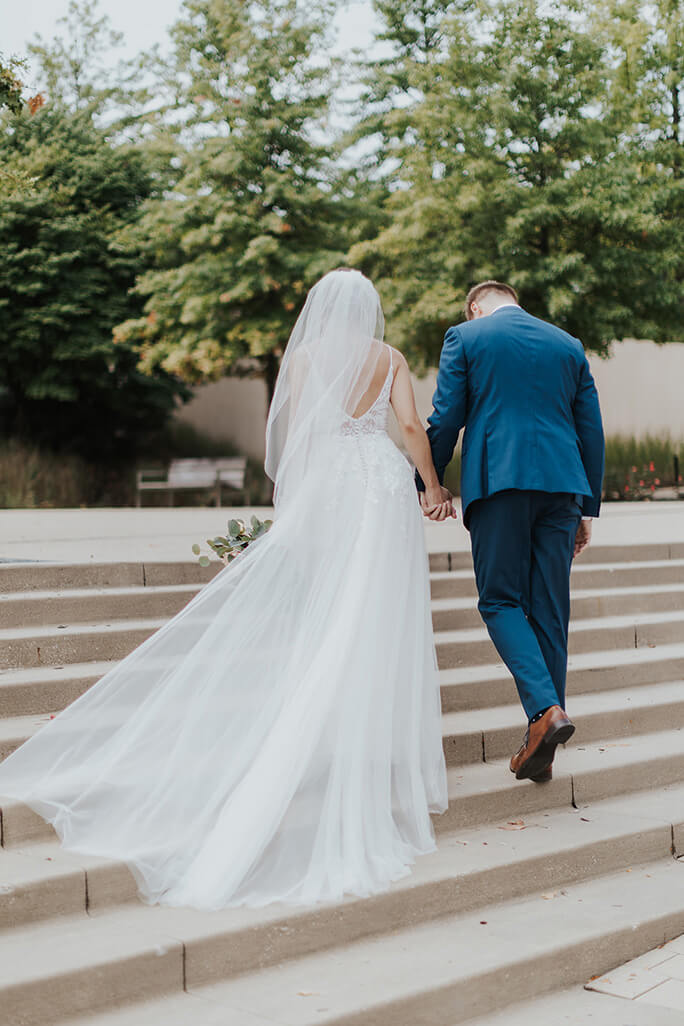 real bride and groom walking up stairs at kauffman center in kansas city - style D2840 by essense of australia